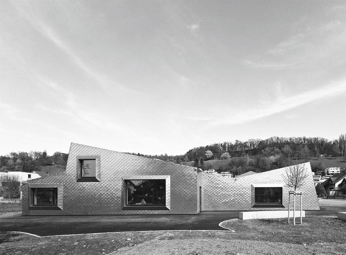 Frontale Längsansicht des mit Messingschuppen verkleideten Kindergartens Zelgli West in Untersiggenthal von Eglin Schweizer Architekten.