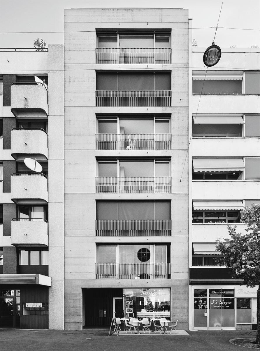 La maison étroite à grandes fenêtres avec la façade en «béton artisanal» et les balustrades aux lignes très fines à la rue du Môle. Architecte: atelier Bonnet architectes EPFL FAS.
