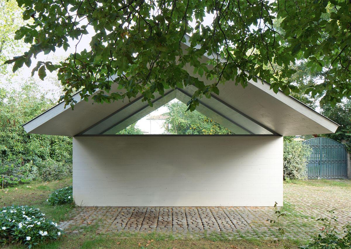 Ein Kartenhaus im Garten, im Niemandsland. Die prekären Auflager der auskragenden Dach-Scheiben sind in der abstrakten Komposition verborgen. Architektur: Studiospazio Bild: Stefano Graziani