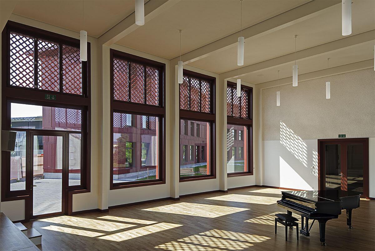 Singsaal der Schulanlage in Ballwil mit Blick auf das Unterrichtsgebäude von Fiechter & Salzmann Architekten.