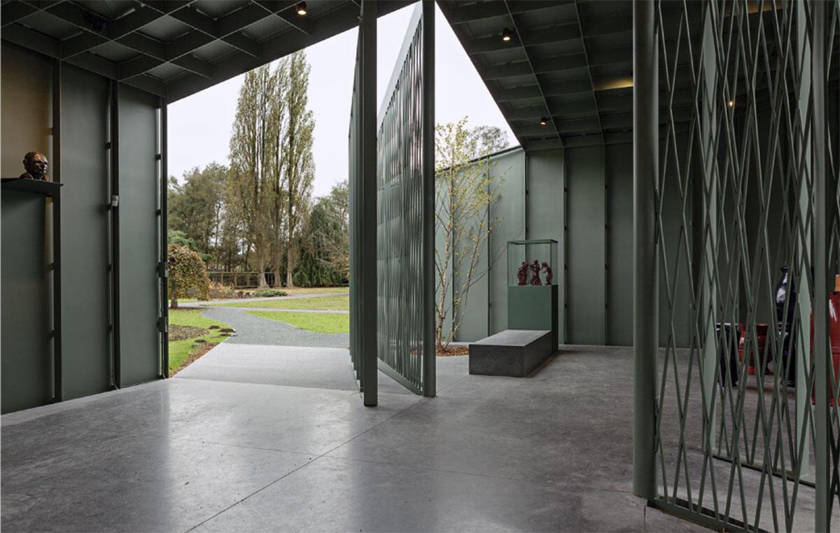 Pavillon des Museums Middelheim von Robbrecht en Daem: Grosse, in das rechteckige Volumen eingeschnittene Öffnungen und ausladende Rampen verweben die «Urhütte» Het Huis mit dem Wegenetz des Skulpturenparcours.