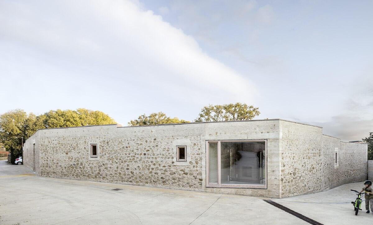 Aus Erde vom Grundstück und mit Steinen der alten Einfriedung errichteten die katalanischen Architekten ein Haus, das wie am Ort üblich den Strassenraum fasst und einen Garten birgt.  Bild: Adrià Goula