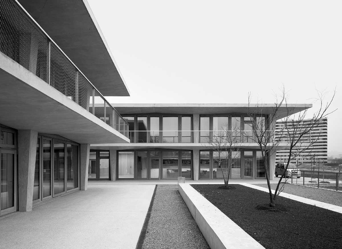 En périphérie de chaque bâtiment, des portiques en béton armé coulé in situ forment une façade durable aux différentes fonctions. La salle de gym et partiellement enterrée. Photos: Rasmus Norlander