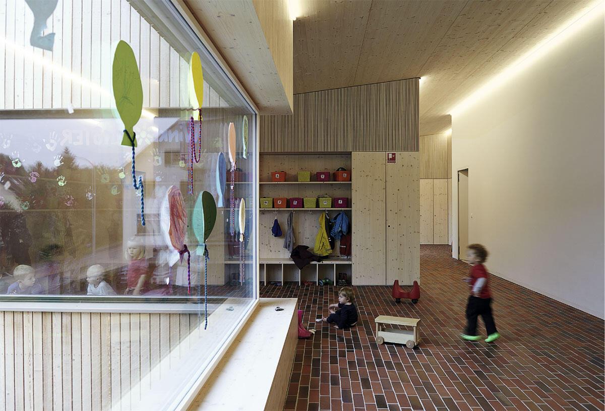 Der Erschliessungsraum mit «städtischem» Klinker als Bodenbelag schlängelt sich durch das Obergeschoss. Kinderkrippe in Stallikon von sabarchitekten, Basel