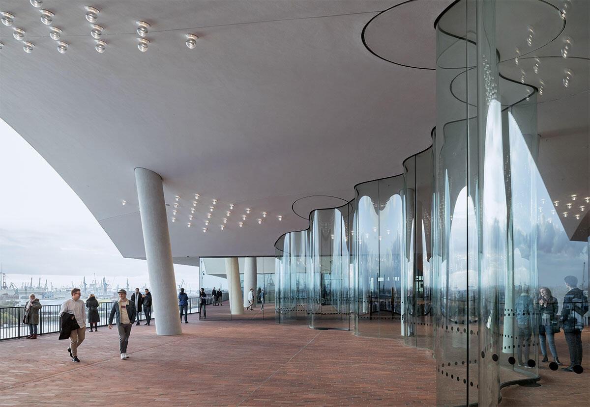 In hohen Bögen öffnet sich die Plaza der Elbphilharmonie zum Umgang. Gewellte Glaswände dienen dem Windschutz. Seitlich davon gelangen die Besucher durch Schleusen ins Freie. Architektur: Herzog & de Meuron