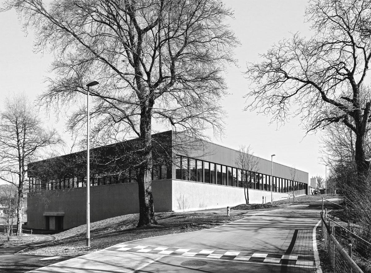 Indem er die Hanglage nutzt, erscheint der Hallenbau am oberen Ende lediglich eingeschossig und nähert sich so dem Massstab des benachbarten Schulhauses an. Architektur: pool Architekten