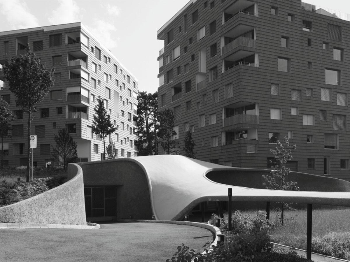 Ansicht von Nordosten mit der Einfahrt in die Tiefgarage. «Wohnen am Bad» in Adliswil von Elmiger Tschuppert Architekten.