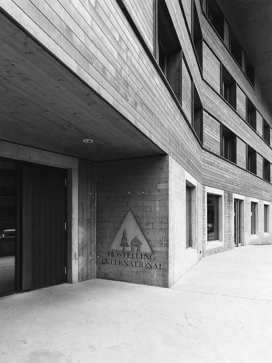 Die einem Oberländer Haus nachempfundene Südfassade umfängt den Eingang zur Jugendherberge Gstaad Saanenland. Architektur: Bürgi Schärer Architektur und Planung AG.