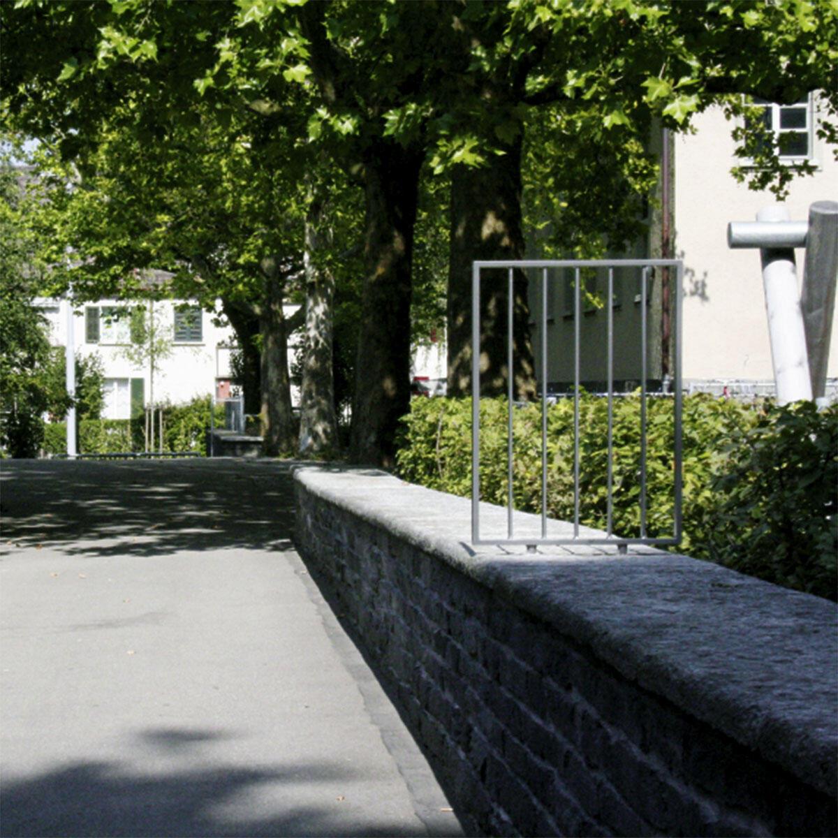 Normierung ad absurdum: Ab einer Höhe von 80 cm müssen Bauteile gemäss der SIA Norm 358 «Geländer und Brüstungen» gegen die Gefahr eines Absturzes gesichert werden; beim Schulhaus Milchbuck in Zürich gilt dies auch für eine Stützmauer, die als Sitzgelegenheit vor gut 80 Jahren entworfen, entlang eines abfallenden Wegs immer höher wird.