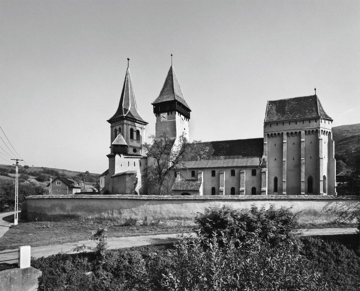 Pfeilerbasilika des 14. Jahrhunderts mit als Wehrturm ausgebautem Chor.