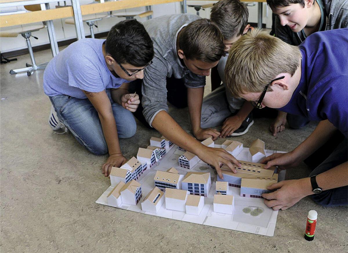 Kinder bauen an der Zukunft des Dorfplatzes Mels. Die HTW Chur entwickelte dafür eigens einen Bastelbogen.