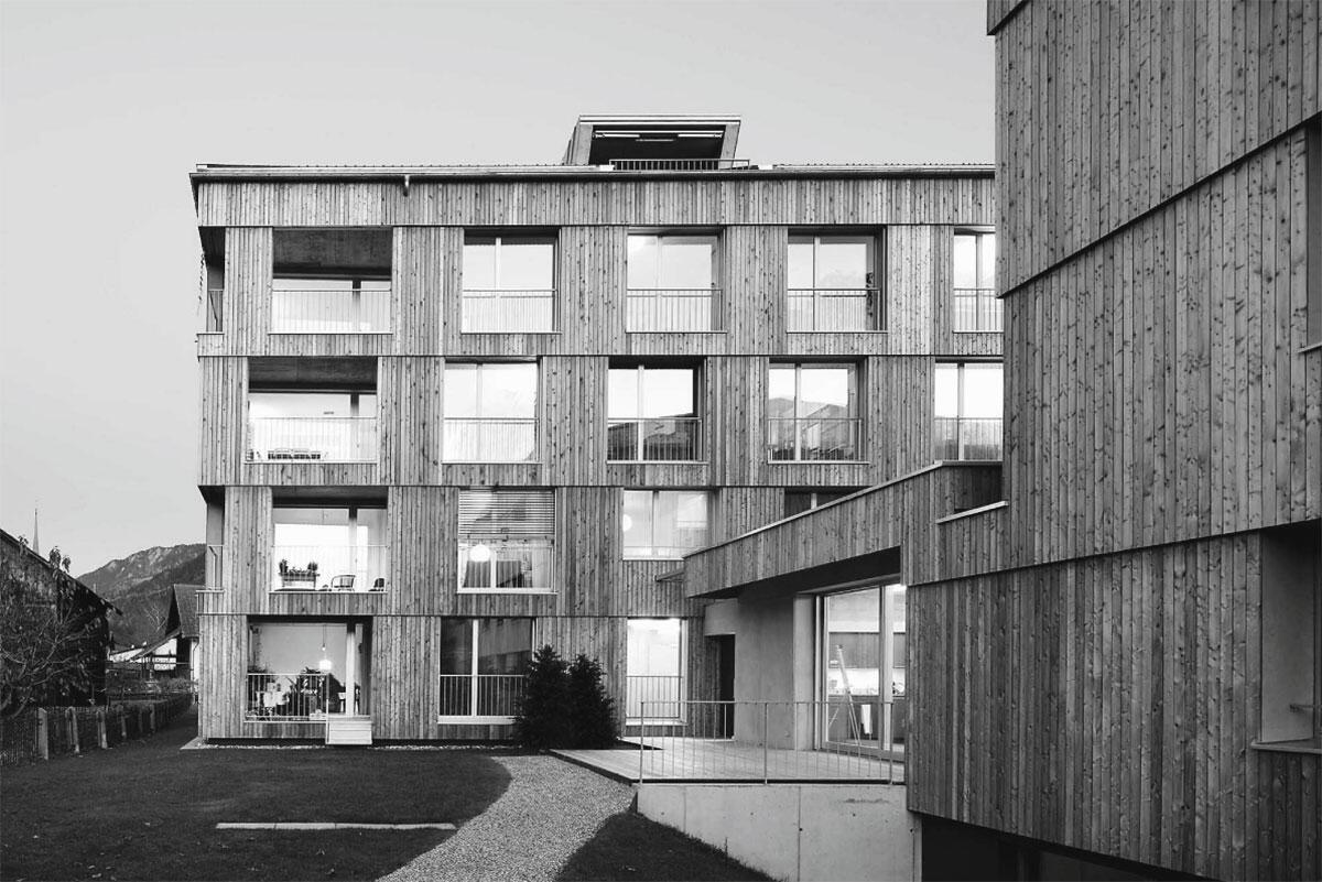 Ansicht von Westen mit der Hofstatt und dem drei- und viergeschossigen Neubau. Genossenschaftliches Wohnen 55+ in Bonaduz von Bürgi Schärer Architektur und Planung, Bern.
