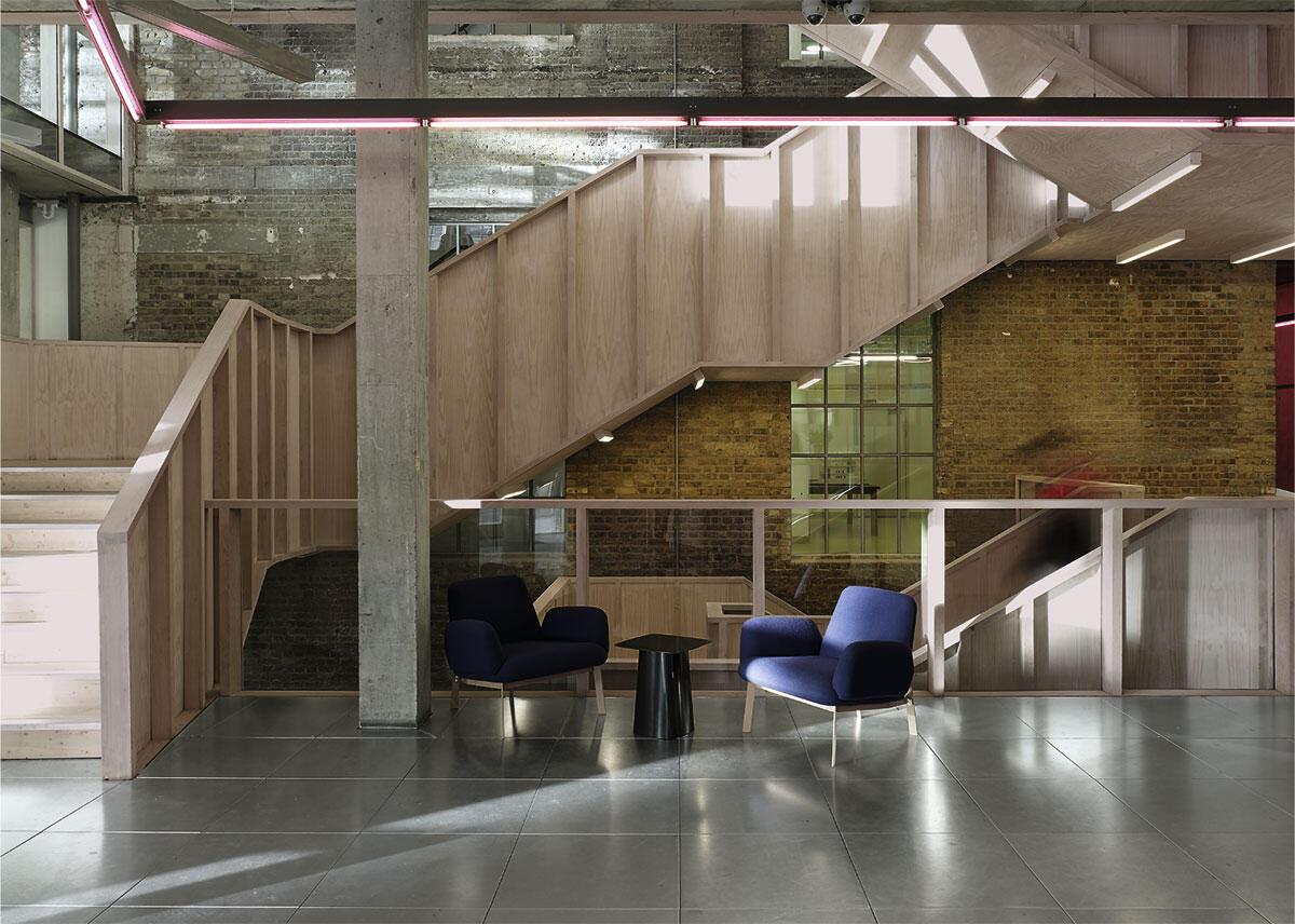 Rückgrat des Hauses der Business School in London ist die grosszügige Treppe, die sich im ehemaligen Innenhof emporschraubt. Unter dem rohen Sperrholz verstecken sich massive Stahlträger, da die geschützte Backsteinfassade keine Lasten aufnehmen konnte. Umbau von Sergison Bates.