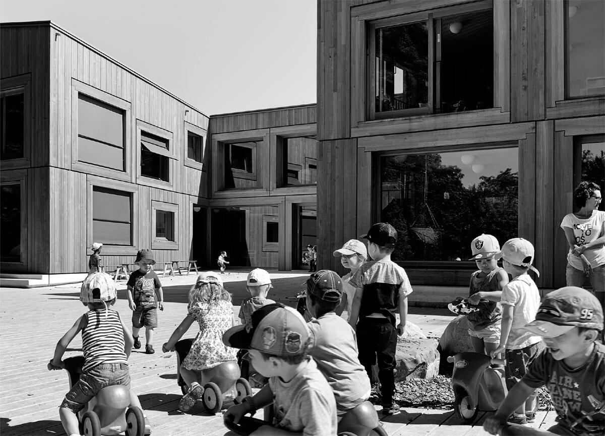 Vue sur le préau de la crèche à la Chapelle-Les Sciers à Lancy qui fonctionne comme une clairière ouverte sur deux grands sapins d'Espagne, en faisant entrer le paysage au coeur du bâtiment. Image: Walter Mair