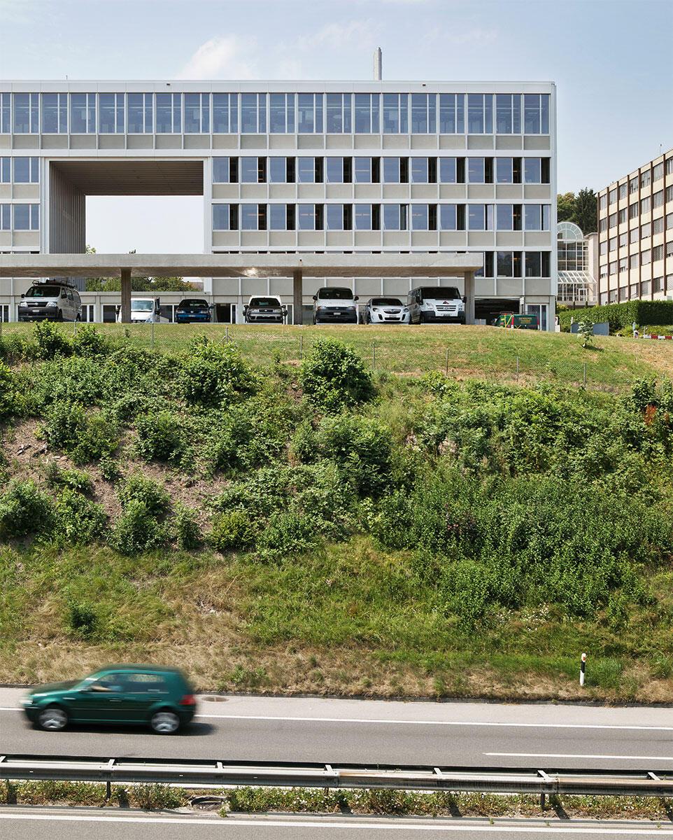 Oberstes Geschoss und Gebäudeteil rechts sind neu gebaut. Vom ehemaligen Provisorium für das Autobahnamt in Givisiez haben Bart & Buchhofer Architekten die Fassade übernommen, sie kleidet nun alle Bauteile einheitlich.