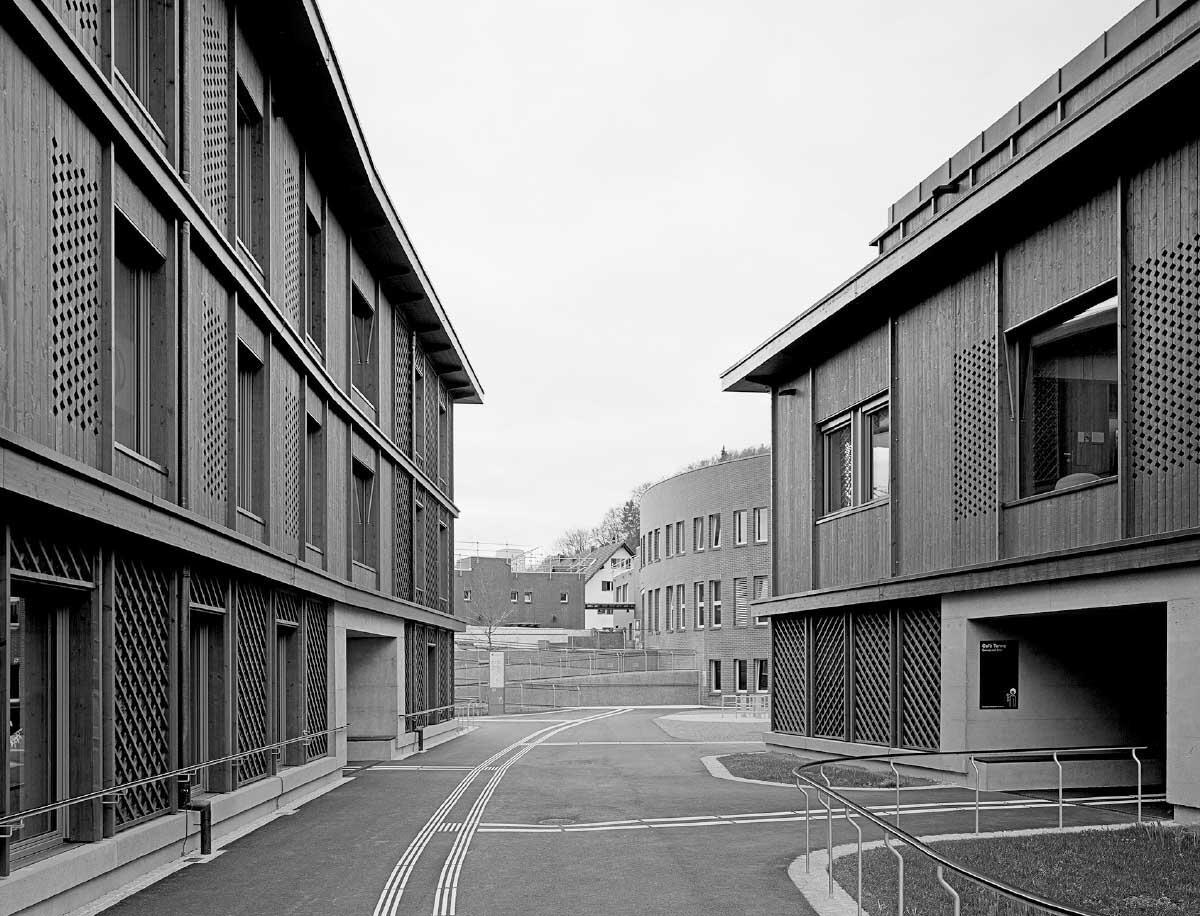 Zwei Baukörper umfassen einen offenen Platz mit Durchblick zum Bestandesbau aus den 1980er Jahren (Baumann Frey). Bild: Rasmus Norlander