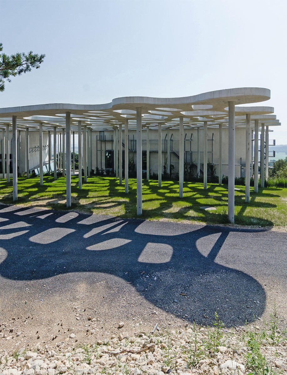Eine offene Säulenhalle trägt ein Gewebe aus Beton, im Hintergrund die Baukörper für das Auditorium und die Bibliothek der Fondation Michalski in Montricher.