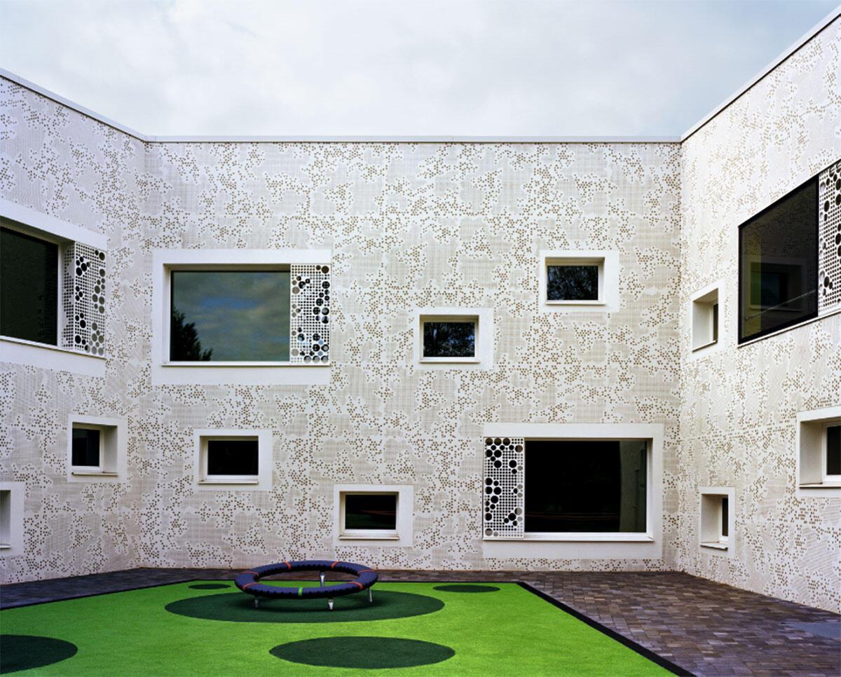 Fassade mit dem grafischen Muster eines schwedischen Schneetarnnetzes