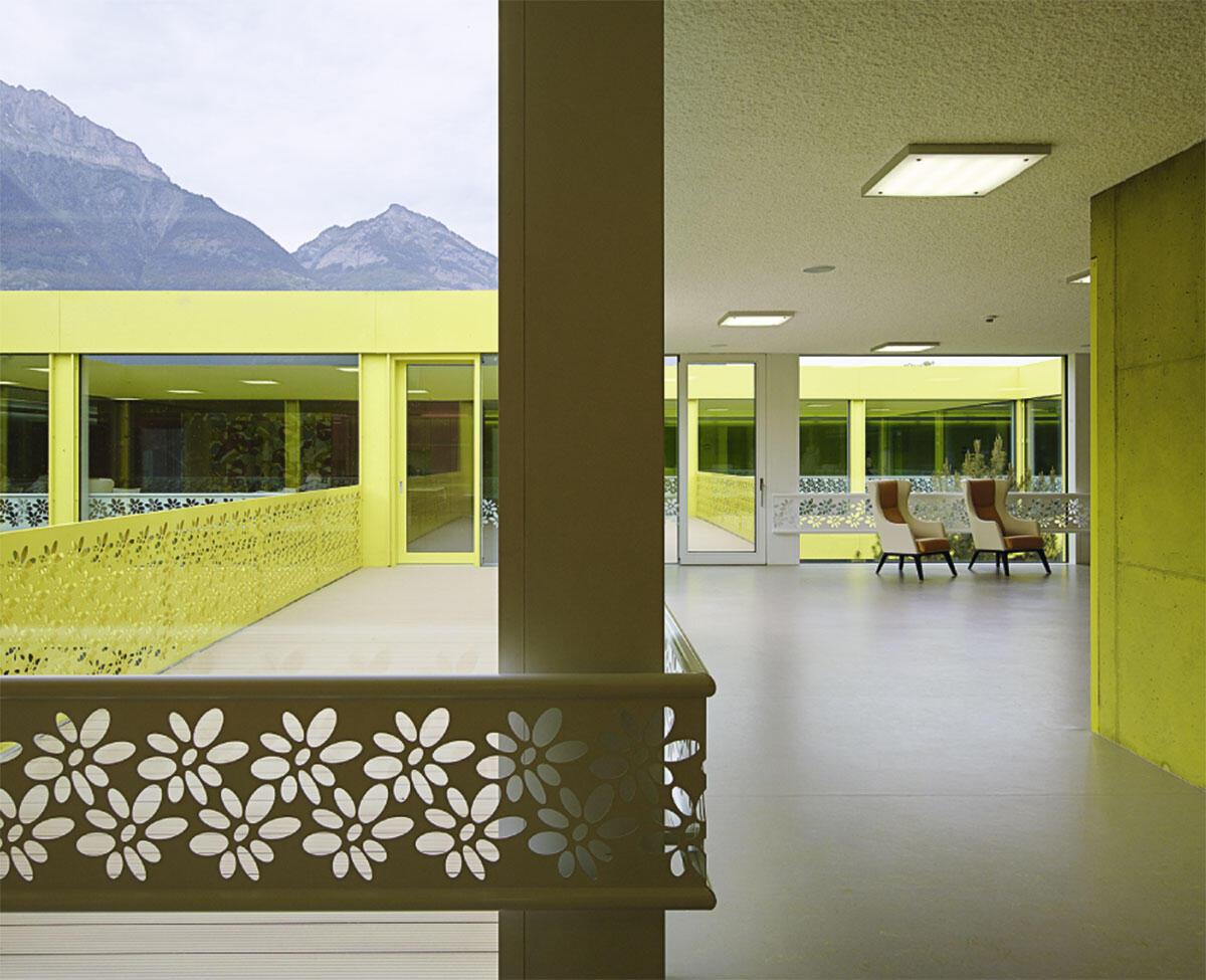 Eine nüchterne Blechfassade charakterisiert das Äussere, verspielte Innenhöfe mit Terrassen das Innere des kommunalen Altersheims von Bonnard Woeffray.