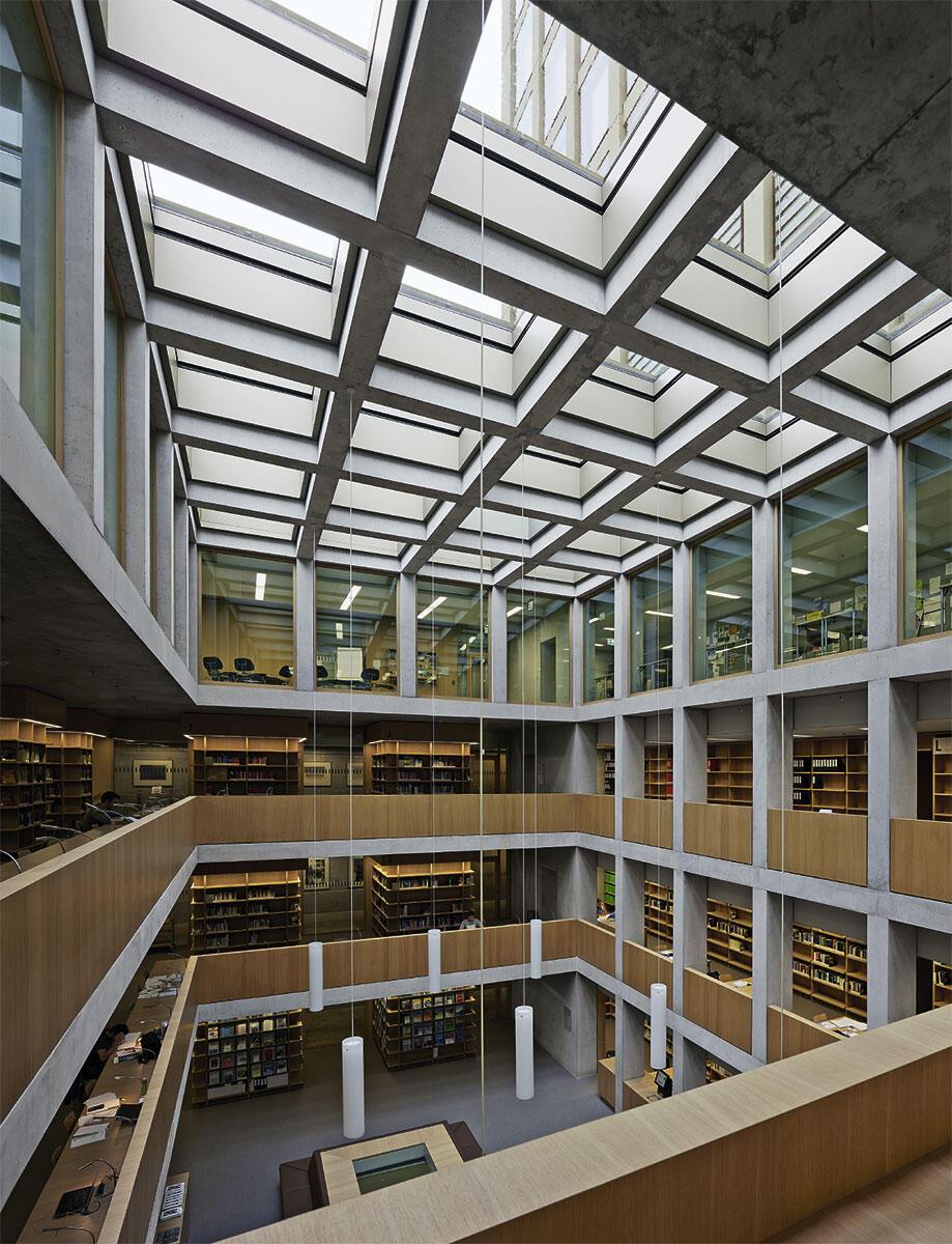 Aufgeschlossene Tektonik: Die vertikalen Lisenen des Turms durcheilen das von Arbeitsplätzen und Bücherregalen bestimmte Raumgefüge der Bibliothek des Fachhochschulzentrums St. Gallen von Giuliani Hönger.