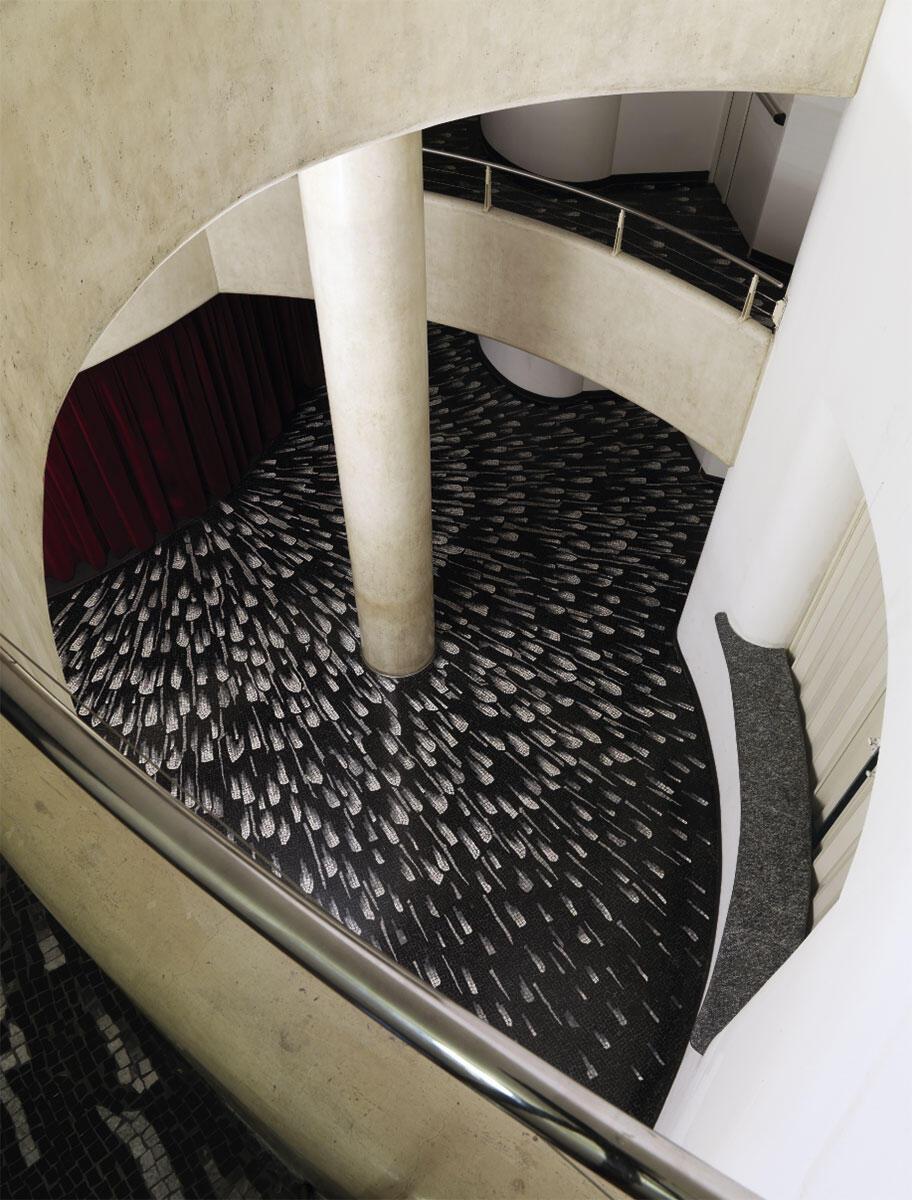 Blick hinab in das Theaterfoyer mit dem tropfenförmigen Mosaik des Künstlers Francesco Somaini, das zum Saaleingang hinführt.