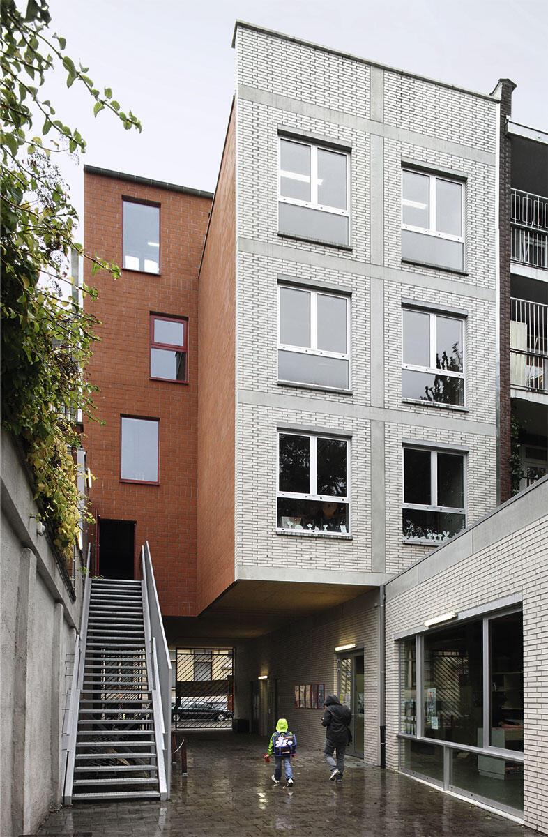 Schule Alberreke in Klein-Antwerpen von Collectief Noord: Von der Strasse her leitet eine helle Backsteinwand in die Tiefe des Hofs. Auf ihr balanciert die Rückfassade des Torbaus. Eine frei stehende Treppe erschliesst die über dem Durchgang liegenden Klassenräume.