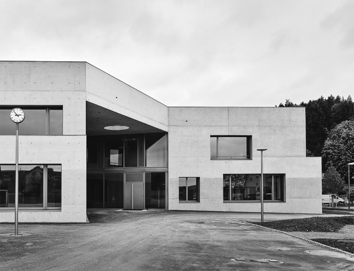 Der Wechsel der Betonbearbeitung und hohe Dachbrüstungen unterstreichen die horizontale Lagerung des Schulhauses Zinzikon von Adrian Streich Architekten Zürich.
