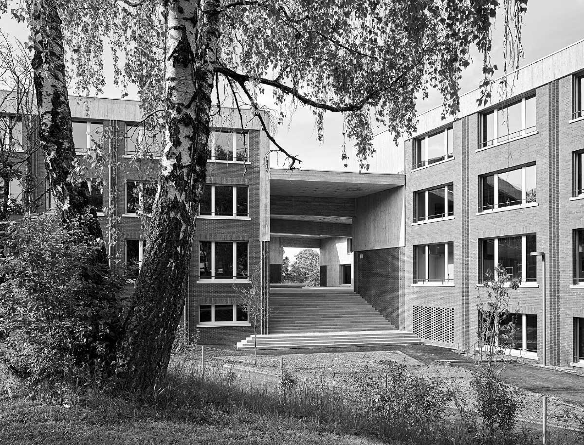 Die selbsttragende Hülle aus Backstein prägt das Äussere der Schule, breite Freitreppen führen zum überdeckten Pausenplatz in der Mitte der Anlage empor. Bild: Roland Bernath