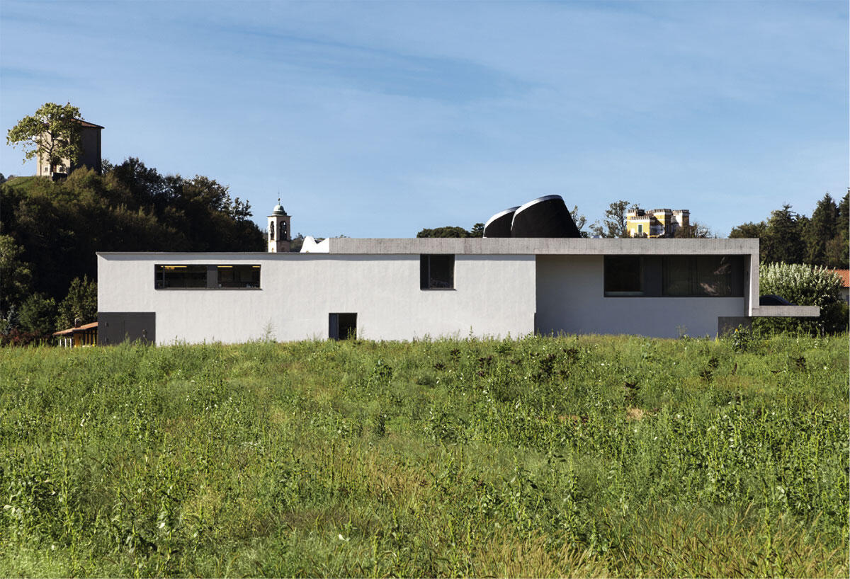 Blick von Norden mit Zugang und Küchenanbau (links) sowie dem gefalteten Dach. Im Hintergrund das «Castello» von Stabio. Architektur: Felix Wettstein, studio we architetti, Lugano.
