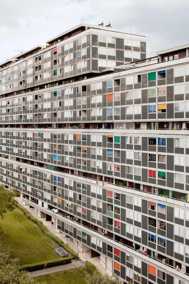 Die Hochhausscheibe schiesst über die Hangkante zum Rhoneufer hinaus, die Erschliessung folgt dem Terrain. Laubengänge und farbige Storen gliedern die schier endlose Fassadenfläche. Bild: Paola Corsini