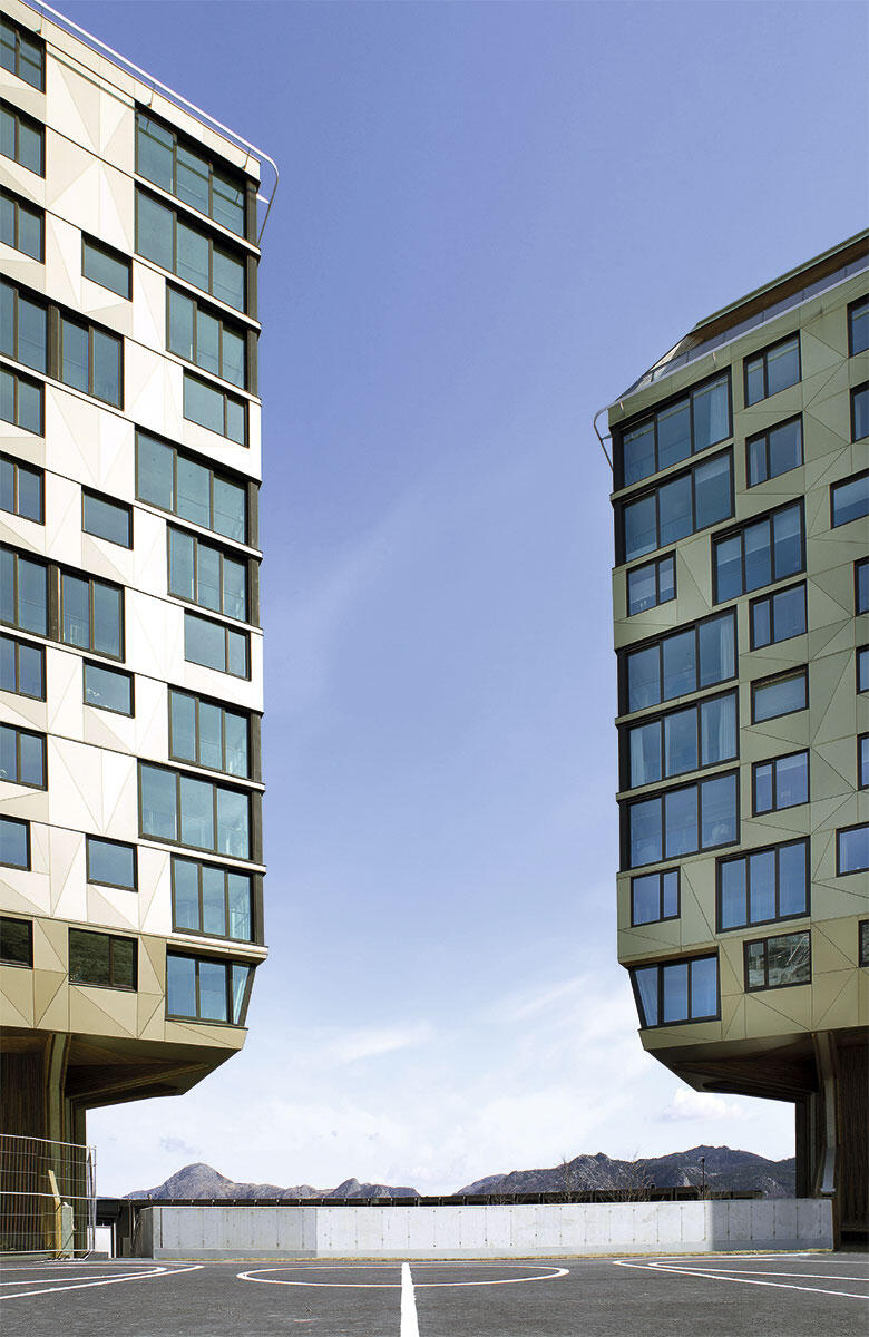 Zwei der drei baumartig auskragenden Wohnhäuser der Siedlung Rundeskogen. Das Basketballfeld reicht bis fast an die Haustüren.