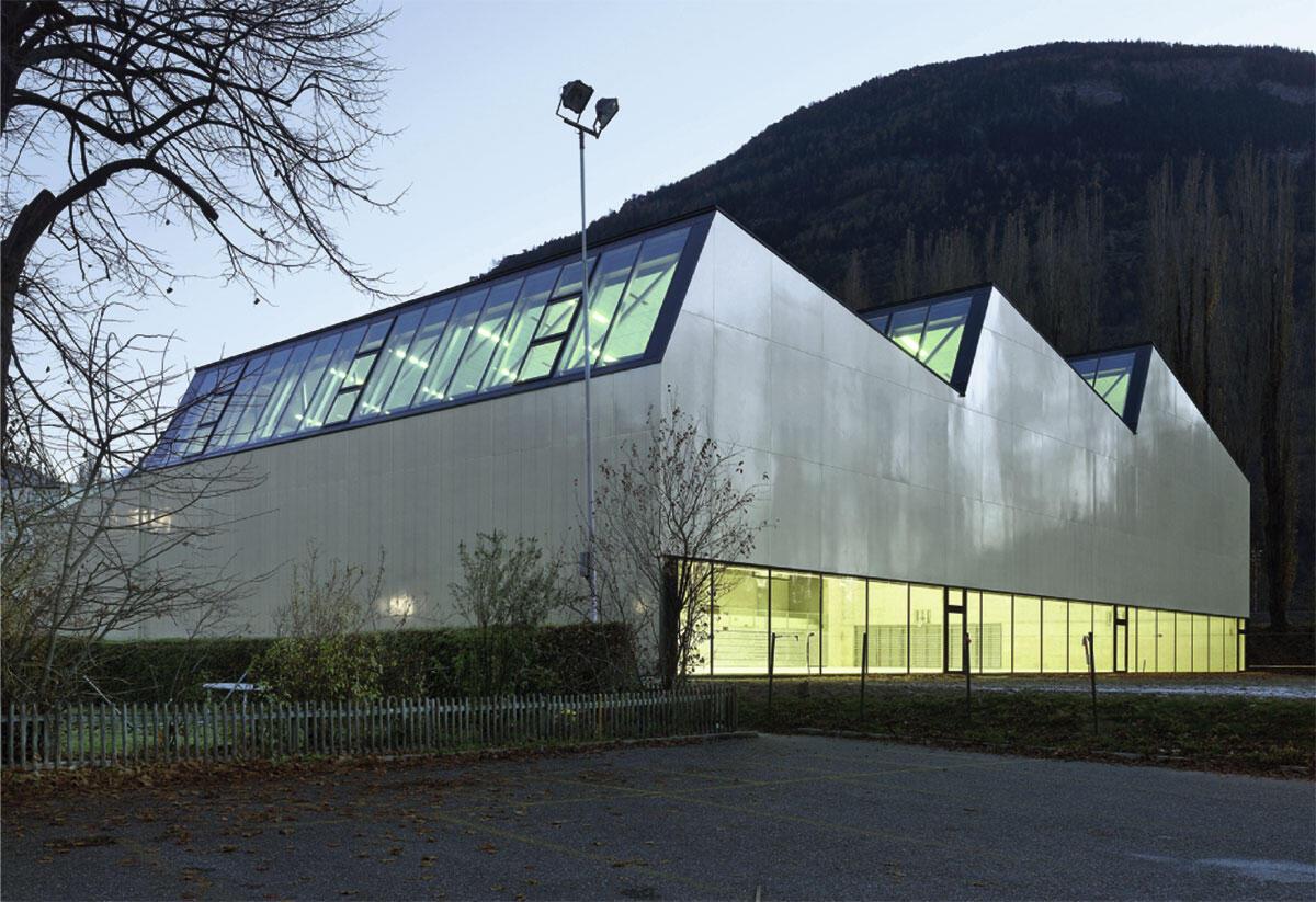Die Sporthalle mit ihrem Sheddach begrenzt den Schulcampus an der Vispa und antwortet den Bergsilhouetten der Umgebung. Architektur von Savioz Fabrizzi und François Meyer architecture.