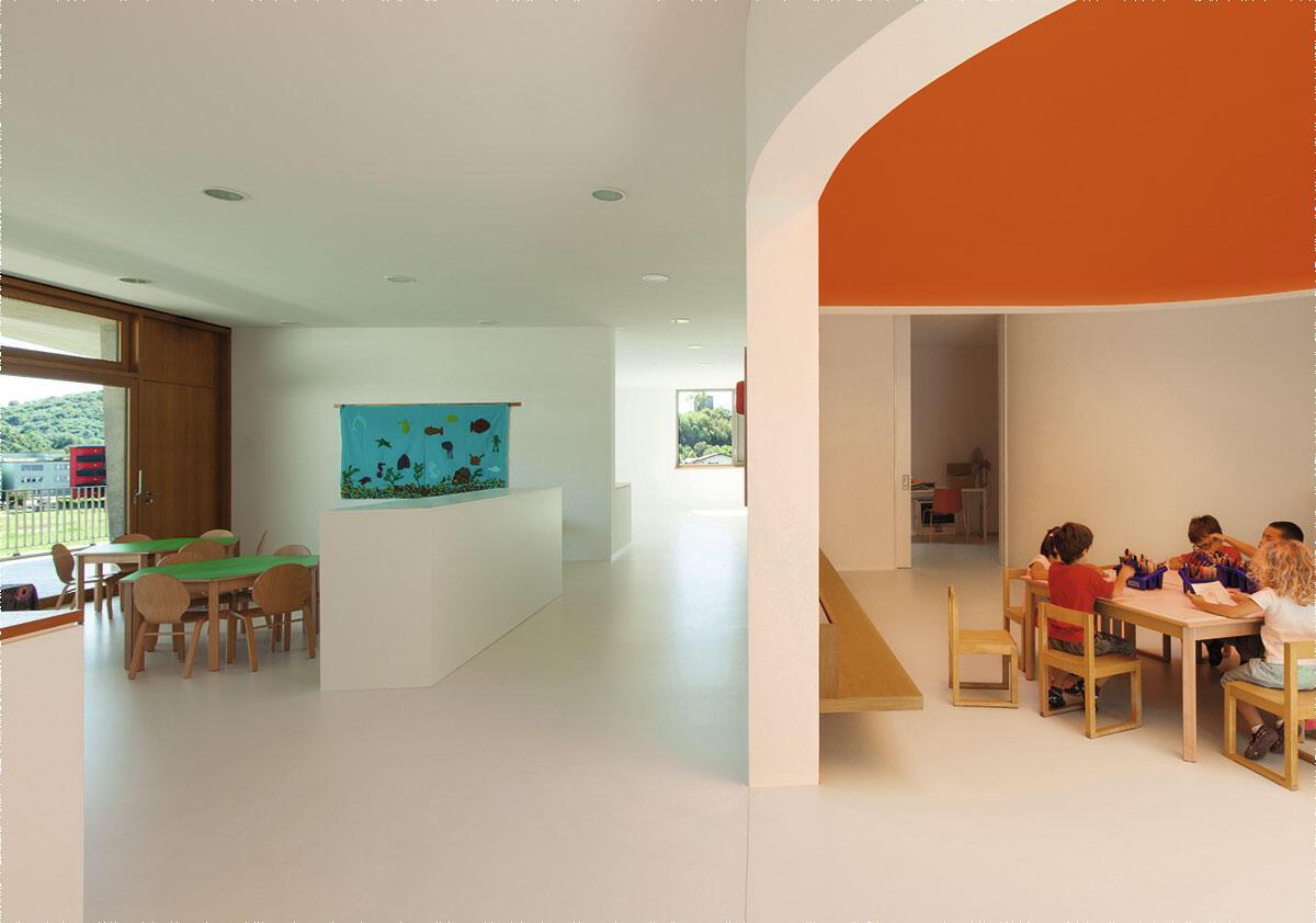 Im Obergeschoss verbindet ein geräumiger Korridor die Spielnischen und Esszimmer der vier Gruppen. Architektur: Felix Wettstein, studio we architetti, Lugano.