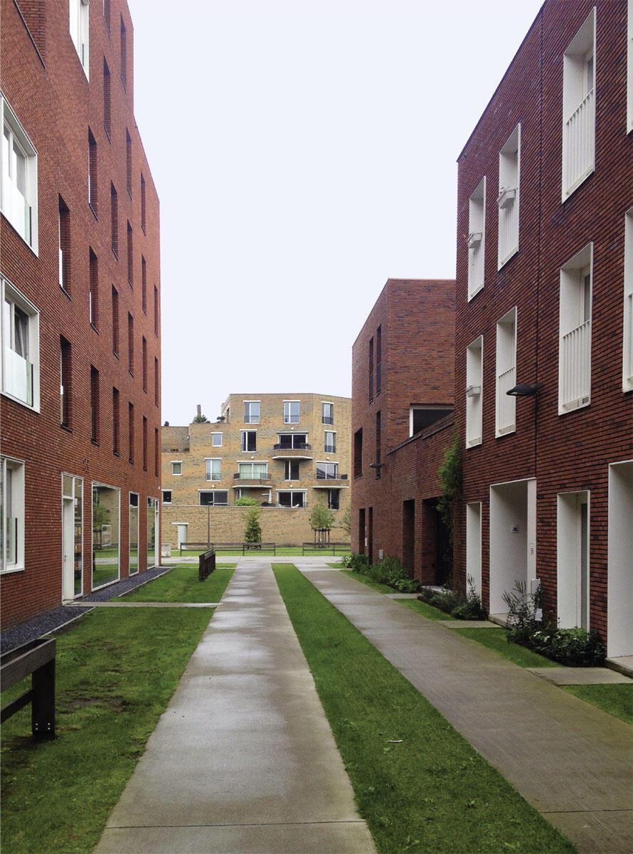Militär-Hospital in Antwerpen: Eine schmale Wohngasse vermittelt zwischen Reihenhäusern von Stéphane Beel und Lieven Achtergael (rechts) und dem höheren Wohnblock an der Nord-Süd-Achse von 360 Architecten (links) sowie dem helleren Torbau am nördlichen Eingang des Areals von Collectief Noord (Hintergrund).