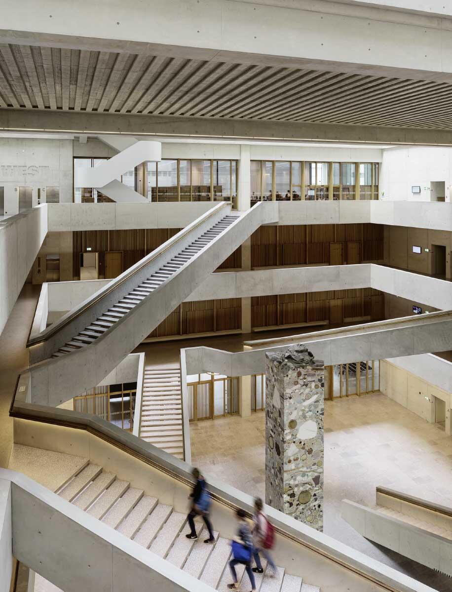 Weit gespannte Treppen verbinden fussläufig die drei unteren Geschosse im grossen Atrium. Die 14 Meter hohe Betonskulptur Nougat von Katja Schenker bildet das symbolische Zentrum des Neubaus. Bild: Andrea Helbling