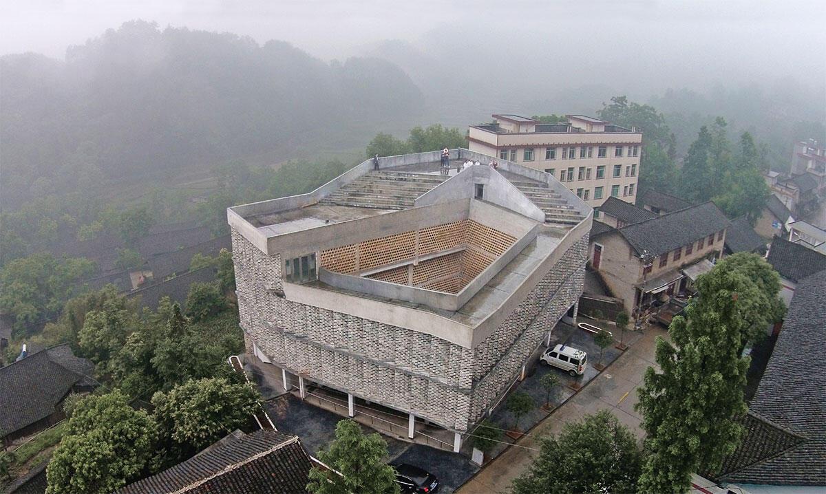 Spital Andong von Rural Urban Framework: Offen und einladend, mit einer Rampe als Erschliessung und einer Hülle aus vorfabrizierten, braunen Betonguss-Elementen.