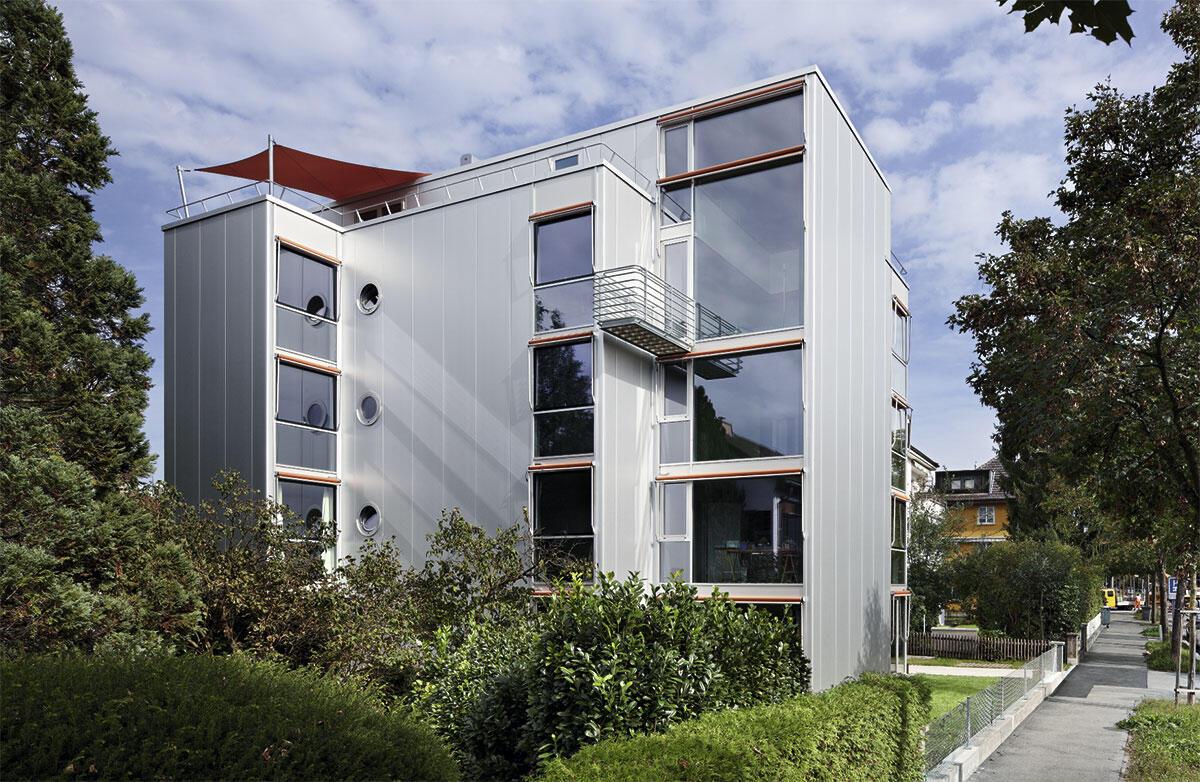 Mit haushohe Paneele trumpft das Wohnhaus in Zürich von Jürg Graser: Die Sandwichelemente reichen über alle Geschosse bis unter das Dach; Ansicht der Westfassade, deren Fenster Blicke in die Tiefe der Regensbergstrasse erlauben.