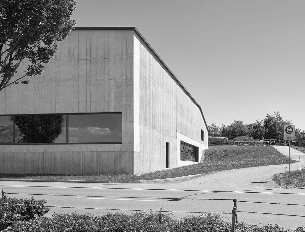 Wie ein Zweckbau steht die Halle am Rand des Dorfs in der Landschaft. Das grosse Fenster zur Strasse macht den Bühnenraum zum Probelokal. Bild: Hannes Herz