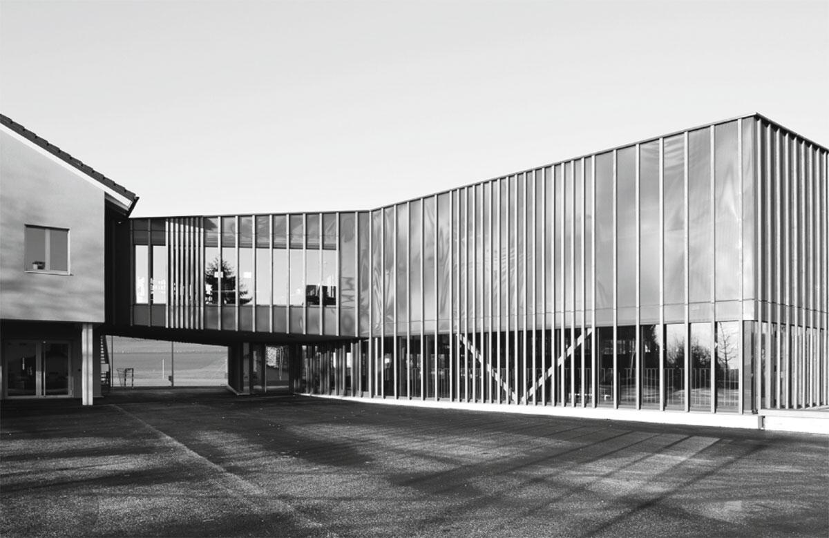 Eine Galerie als Eingangsfoyer gibt der Doppelturnhalle in Auw einen festlichen Zugang. Architektur: GXM Architekten