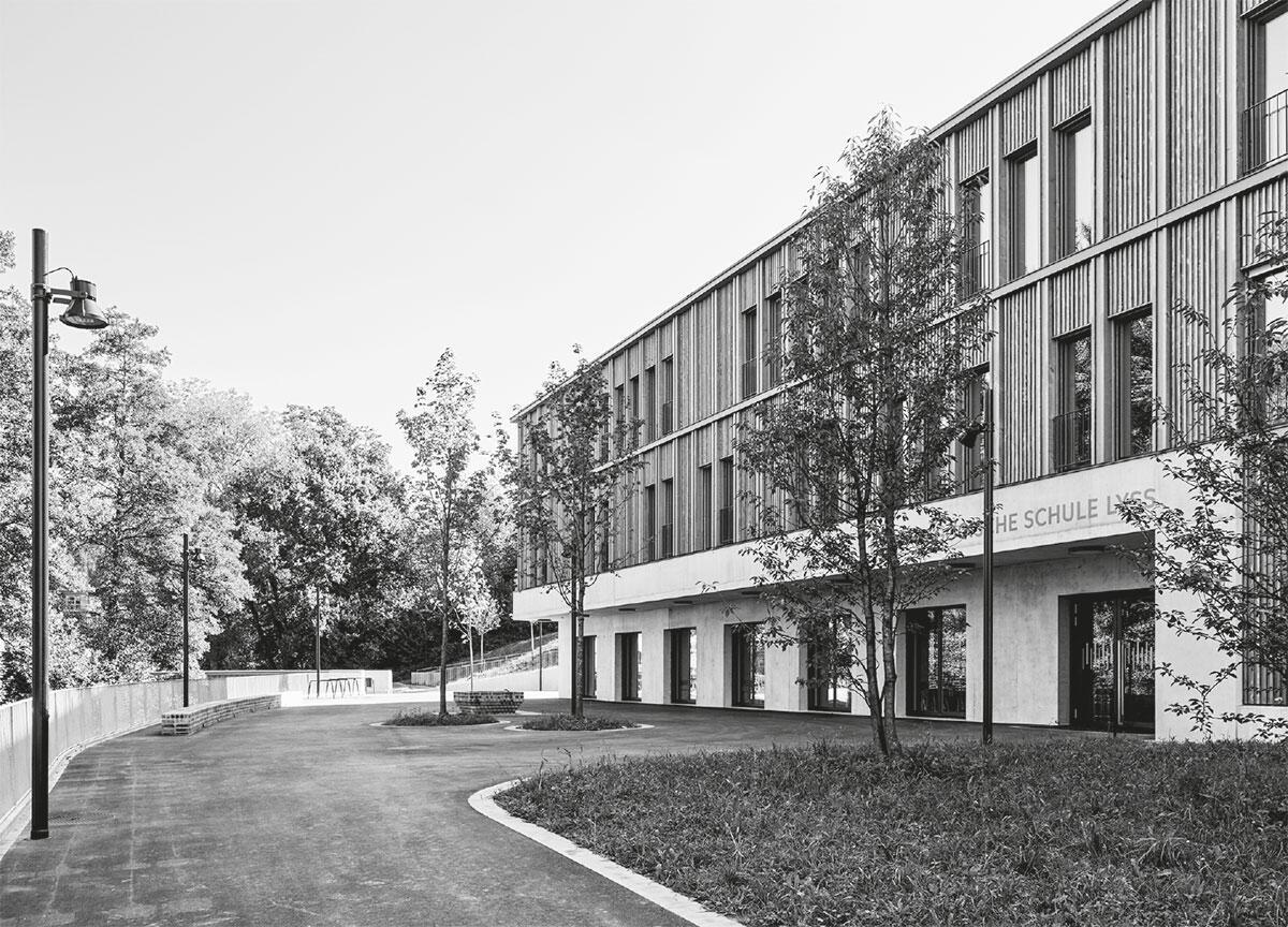 Konstruktiver Holzbau und tektonisch strukturierte Rasterfassade prägen die oberen Geschosse der Heilpädagogischen Schule in Lyss mit Klassen und Büros über dem Sockel aus Beton. Architektur: Met Architektur