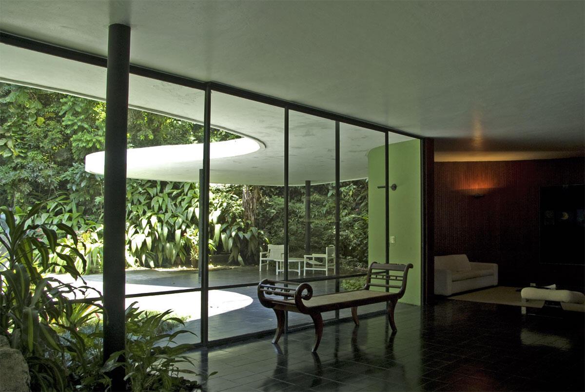 Blick aus dem Wohnraum von Oscar Niemeyers Haus in Rio de Janeiro durch die Verglasung zur Eingangsterrasse.