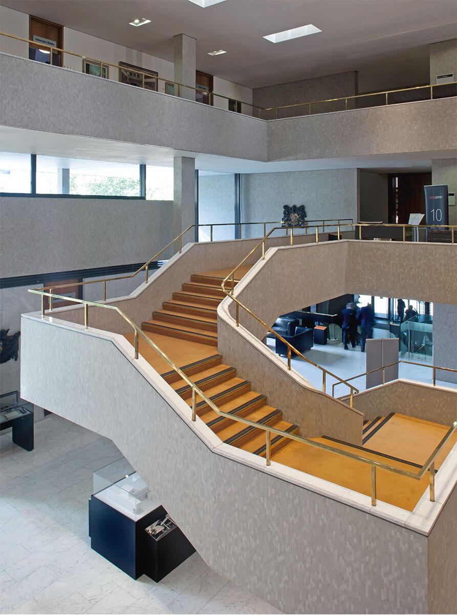 Die frei schwingende Treppe bildet das Herzstück der Halle und des Zeremoniells der traditionsbewussten Institution des Ärzteverbandes. Der Aufgang in die Beletage gleicht einem Prozessionsweg; das Foyer ist ein einziger grosser Begegnungsort.