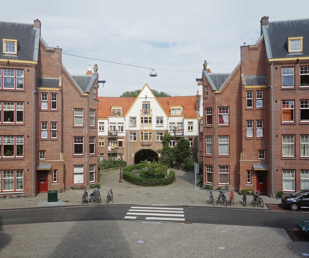 Eingang zum Zaanhof-Komplex in Amsterdam (Johan van der Mey, ab 1913). Eine Cour d'honneur eröffnet die Überbauung, hinter der Hofdurchfahrt verbirgt sich der halböffentliche Dorfanger mit doppelter Randbebauung.  Bild: Alamy Stock
