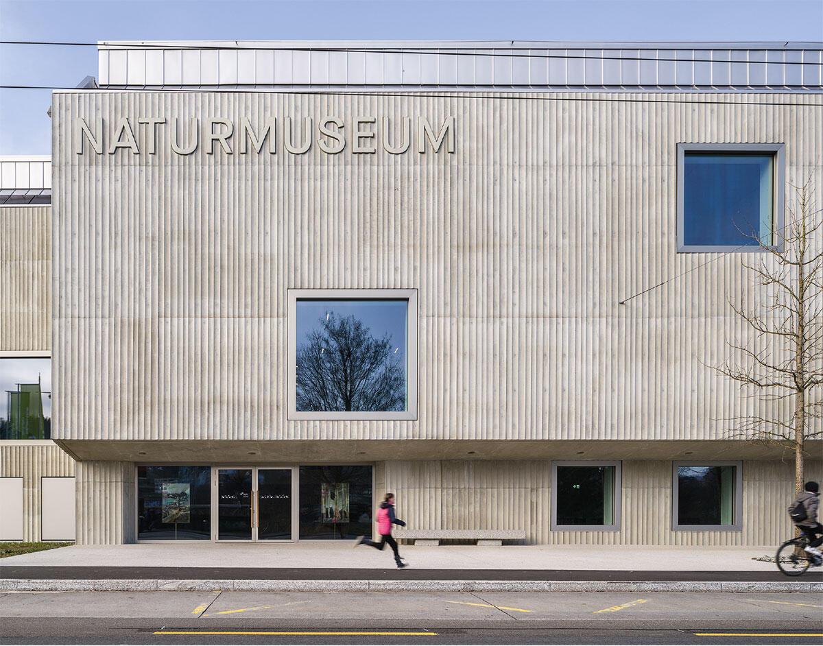 Ambiguität macht den Reiz: Gewächshaus-Dächer und kannelierte Fassaden verorten den Bau zwischen Agro-Industrie und Kunstmuseum um 1900. Der Eingang ist auch eine Bushaltestelle.