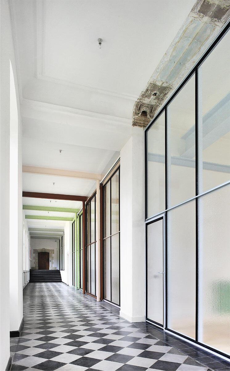 Büros famous: Eine Glaswand ersetzt die tragende Wand; die Farbe der Fensterprofile verweist auf die vorgefunden Farben der Räume dahinter. Ein Umbau von De Vylder Vinck Taillieu.