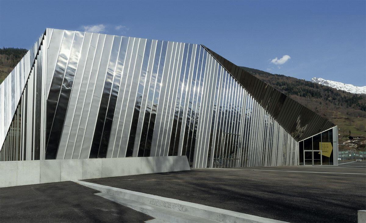 Die kristallartige Geometrie ist mit spiegelnden Blechbändern umschlossen. Espace St-Marc in Châble von Voltolini architectes und Jean-Paul Chabbey.