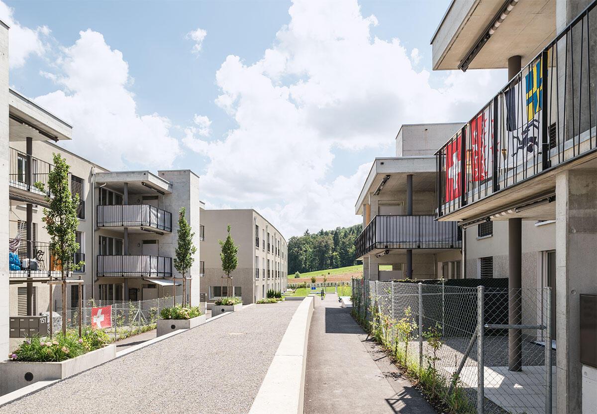 Nach aussen hin zeigt sich die Siedlung Oberwis in Winterthur-Dättnau kompakt und geschlossen; sie öffnet sich nach innen zum gemeinschaftlichen Hof, wo private und gemeinschaftliche Bereiche sehr eng verzahnt sind. Architektur: Jakob Steib Architekten. Bild: Pit Brunner