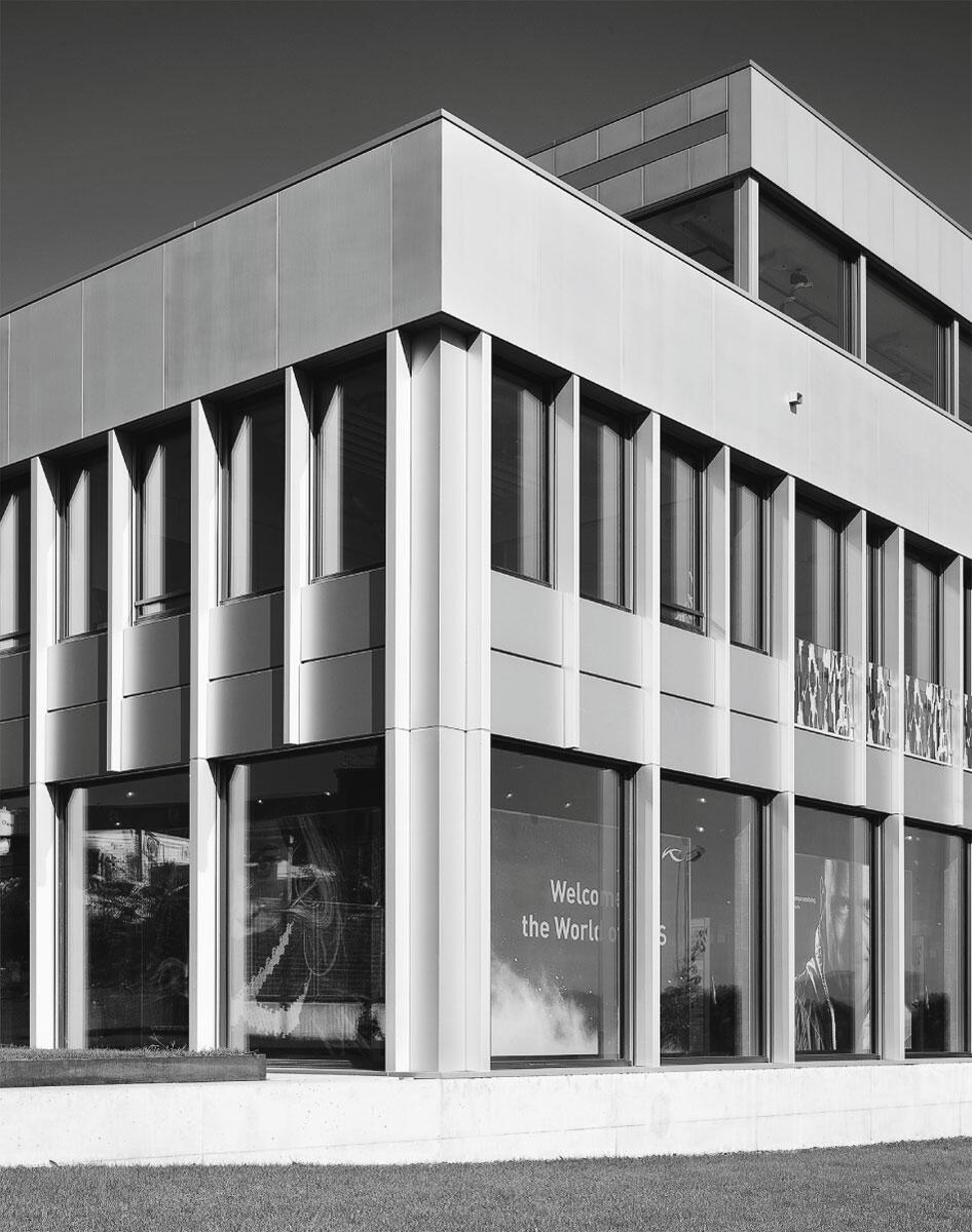 Zarte Lisenen konstrastieren mit dem breiten Brüstungsband vor der Attika: Neubau Geschäftshaus in Hünenberg von Oswald Irriger Wirz Architekten.