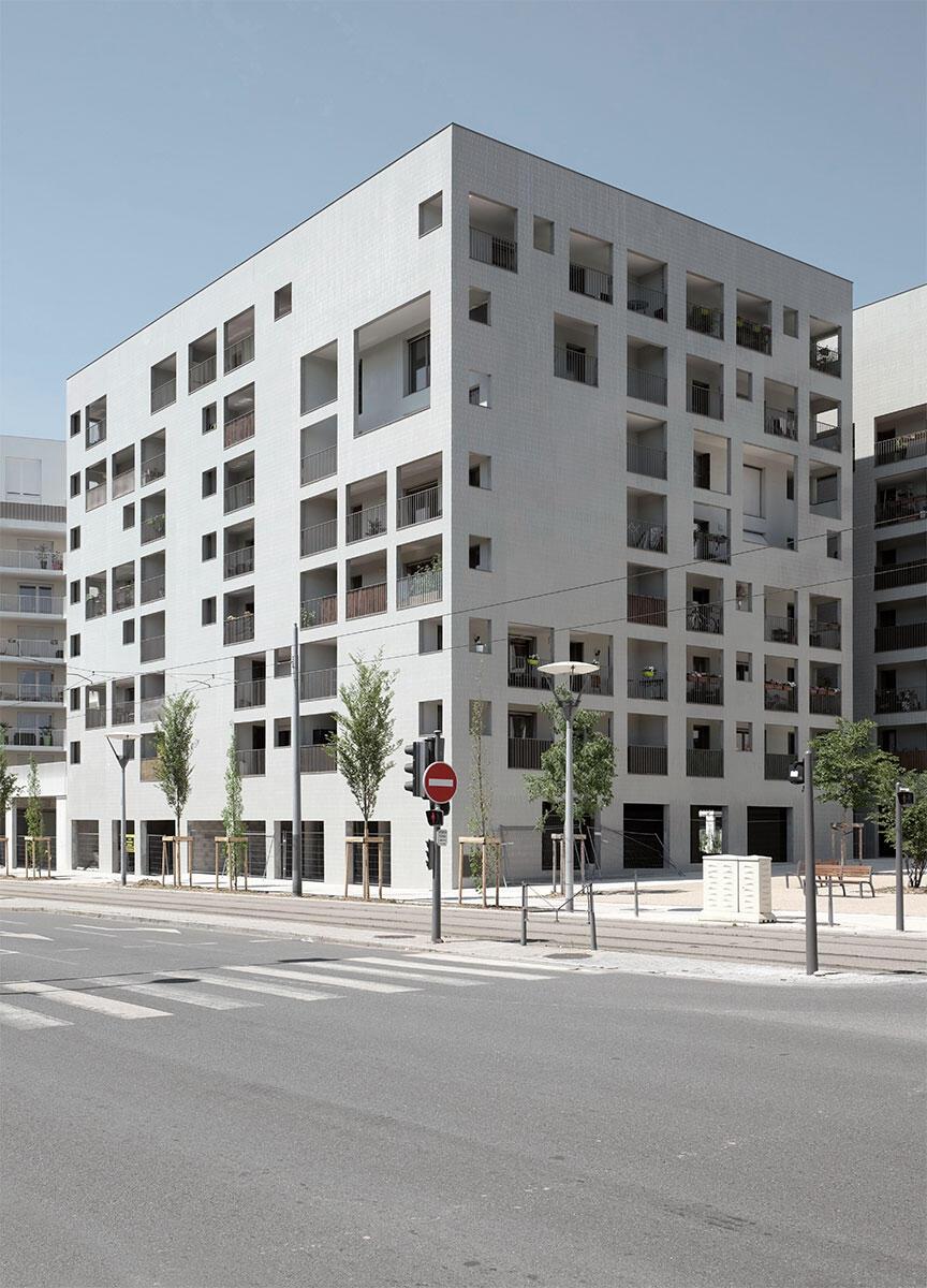 Zwei abstrakt wirkende Kuben ohne Sockel am Eingang zum neuen Stadtquartier in Lyon: Die Lochfassade des Wohnensemble von Eric Lapierre verleiht den Bauten ihr Gesicht und den Loggien dahinter eine beschirmende Schale.
