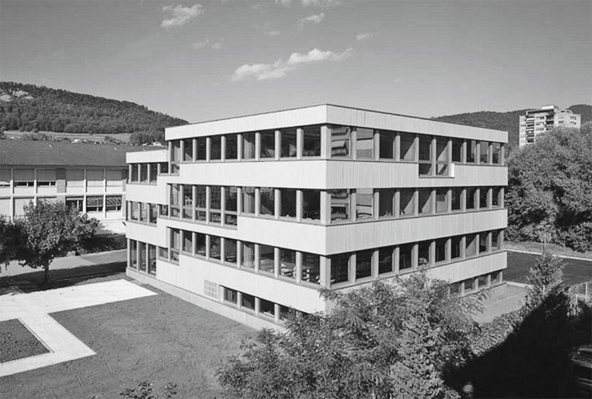 Erweiterungsbau Collège de Delémont von GXM Architekten, Zürich: Ansicht des Erweiterungsbaus von Südwesten, im Hintergrund der Altbau aus den 1950er Jahren.